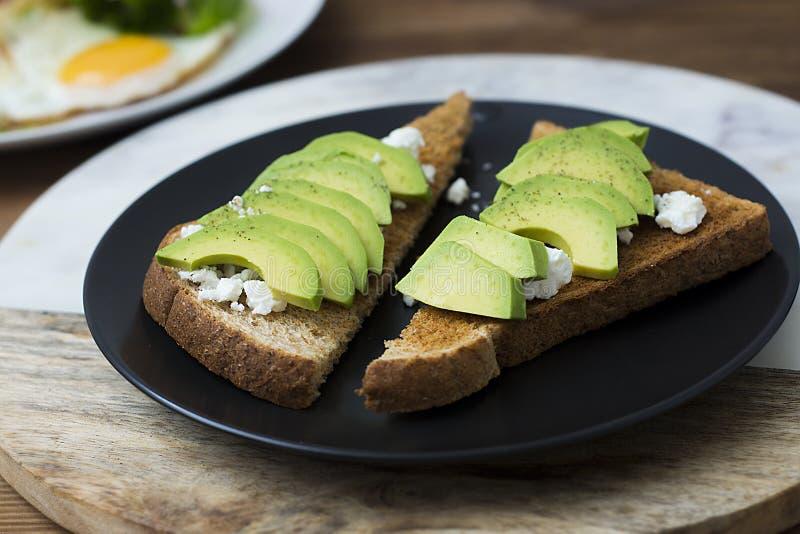 El bocadillo del desayuno en el pan de la tostada hizo con el aguacate, el queso cremoso y las semillas cortados frescos, desde a foto de archivo libre de regalías