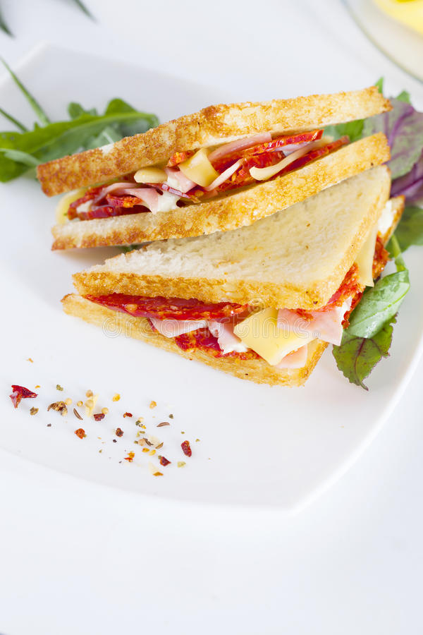 El bocadillo dos con el jamón y el queso untan con mantequilla las especias, salchicha, salchichones, chorizo imagen de archivo