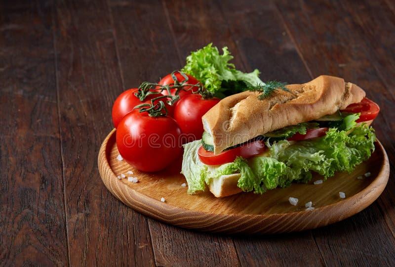 El bocadillo fresco con lechuga, los tomates y el queso sirvió en la placa de madera sobre el fondo de madera, foco selectivo foto de archivo libre de regalías
