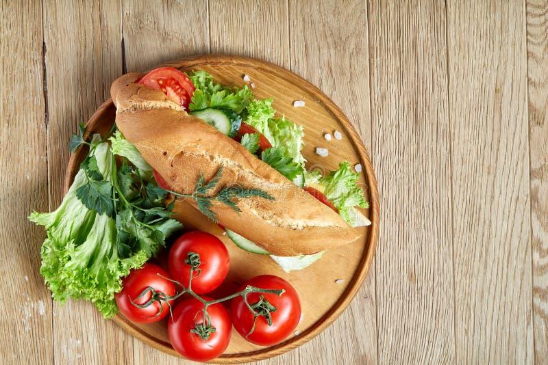 El bocadillo fresco con lechuga, los tomates y el queso sirvió en la placa de madera sobre el fondo rústico, foco selectivo foto de archivo