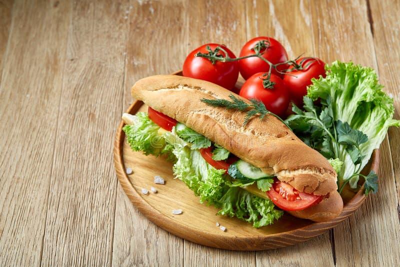 El bocadillo fresco con lechuga, los tomates y el queso sirvió en la placa de madera sobre el fondo rústico, foco selectivo imagenes de archivo