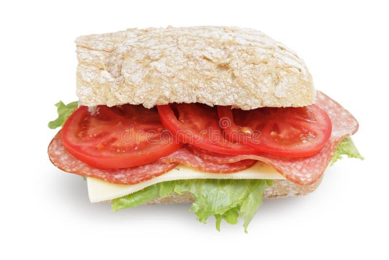 El bocadillo grande con el tomate y la ensalada del queso del salami se va en el pan del ciabatta imagen de archivo