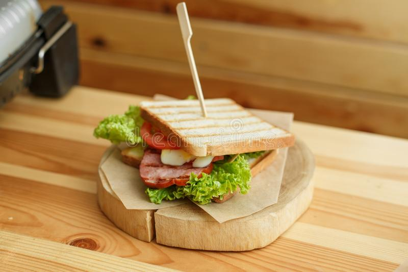 El bocadillo jugoso con pan asado a la parrilla y el tocino le esperan en la placa de madera imagen de archivo libre de regalías