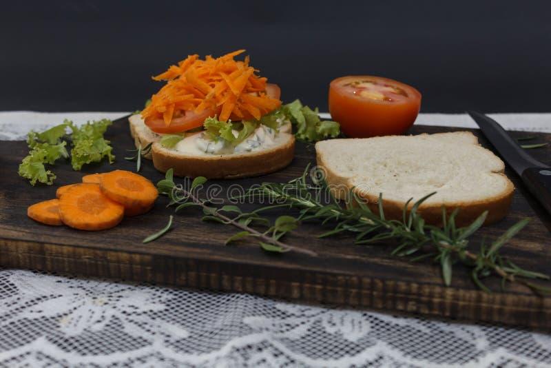 El bocadillo vegetariano sano con la zanahoria, tomate, lechuga y especias, sirvió en un tablero de madera imagen de archivo