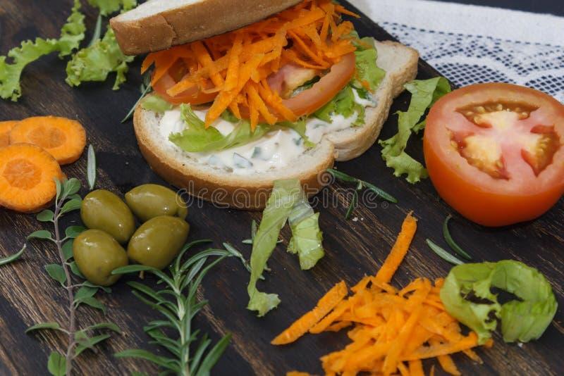 El bocadillo vegetariano sano con la zanahoria, tomate, lechuga y especias, sirvió en un tablero de madera fotografía de archivo