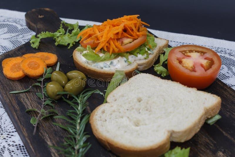 El bocadillo vegetariano sano con la zanahoria, tomate, lechuga y especias, sirvió en un tablero de madera imagenes de archivo