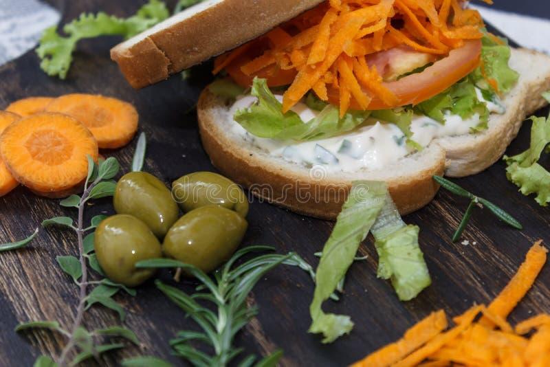 El bocadillo vegetariano sano con la zanahoria, tomate, lechuga y especias, sirvió en un tablero de madera fotos de archivo