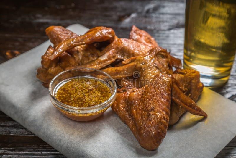 El bocado a las alas de pollo ahumadas de la cerveza con una salsa de la mostaza granosa en el tablero para archivar se cubre con imágenes de archivo libres de regalías