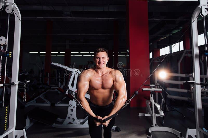 El bodybuider fuerte grande sin las camisas demuestra ejercicios de la cruce Los músculos pectorales y el entrenamiento duro foto de archivo libre de regalías