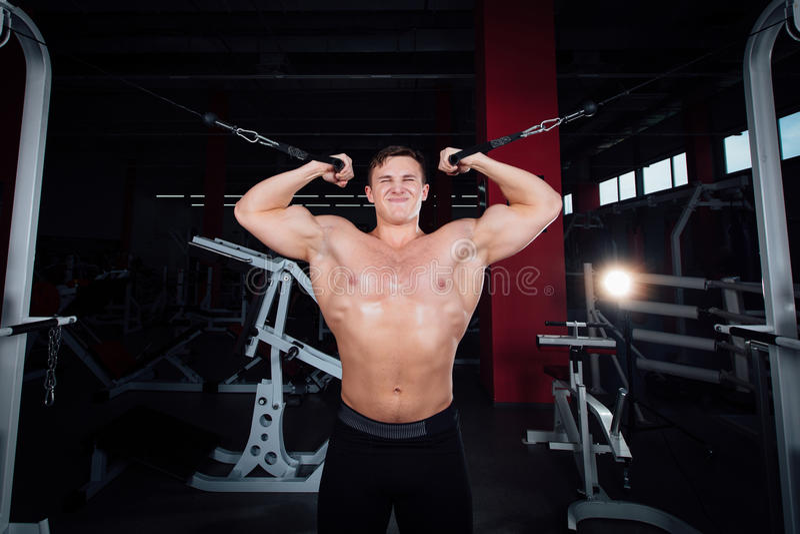 El bodybuider fuerte grande sin las camisas demuestra ejercicios de la cruce Los músculos pectorales y el entrenamiento duro foto de archivo