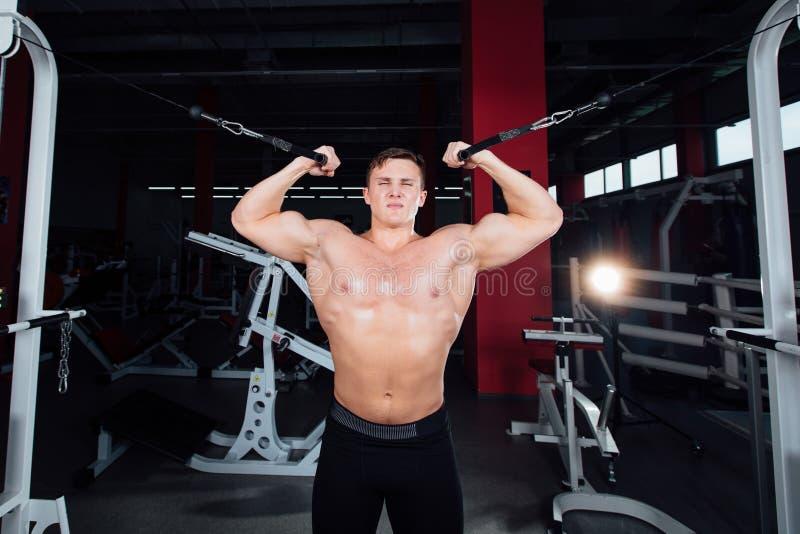 El bodybuider fuerte grande sin las camisas demuestra ejercicios Los músculos pectorales y el entrenamiento duro foto de archivo