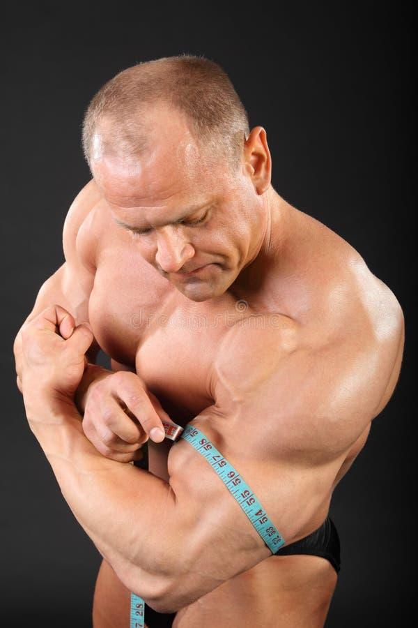 El Bodybuilder mide la talla del bíceps foto de archivo libre de regalías