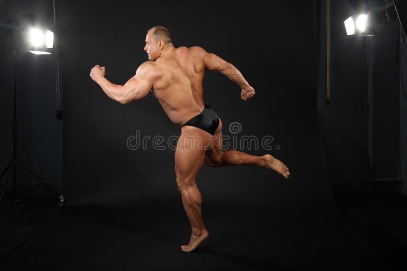 El Bodybuilder toma la actitud agraciada de ejecutarse imagen de archivo