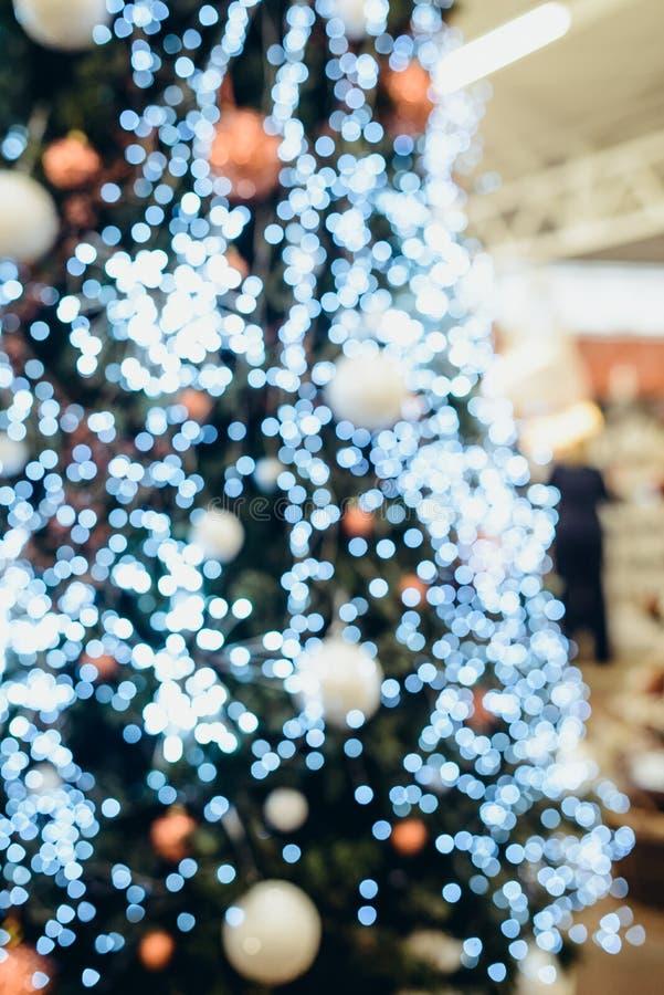 El bokeh borroso siluetea del árbol de navidad con las luces y las bolas de oro Fondo vertical con el espacio de la copia para el fotos de archivo libres de regalías