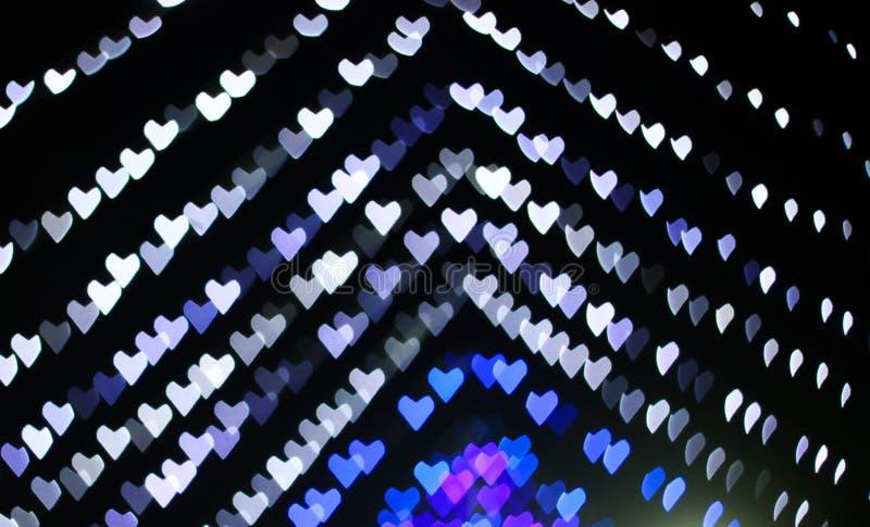El bokeh en forma de corazón blanco y el azul colorearon listo para su capa del diseño imágenes de archivo libres de regalías