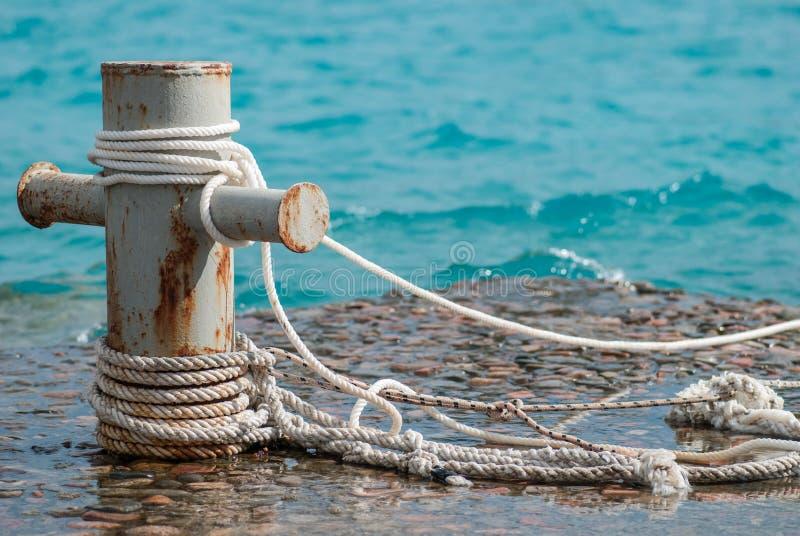 El bolardo oxidado del amarre con las cuerdas de la nave y el mar claro del turquouse ocen el agua en fondo fotografía de archivo