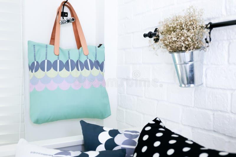 El bolso colgó en la pared de ladrillo blanca con las almohadas coloridas fotografía de archivo libre de regalías