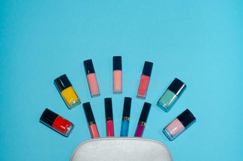 El bolso cosmético de la mujer, compone productos de belleza en fondo azul Lápices labiales rojos, rosados, magentas y azules Sis imagenes de archivo