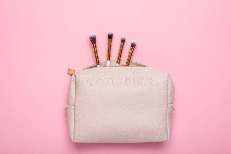El bolso cosmético de las mujeres con los cepillos del maquillaje en un fondo rosado imagenes de archivo