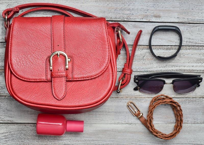 El bolso de cuero rojo y la otra disposición femenina de los accesorios en un escritorio de madera Visión superior Tendencia del  imagen de archivo
