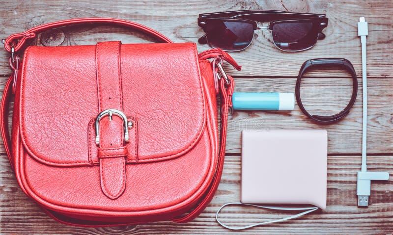El bolso de cuero rojo y la otra disposición femenina de los accesorios en un de madera imagen de archivo