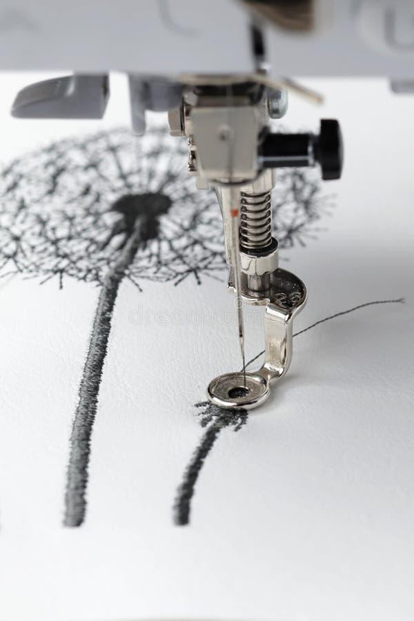 el bordado con la máquina del bordado - dandilon en la piel sintética blanca - opinión macra del detalle sobre área de costura y  fotografía de archivo libre de regalías