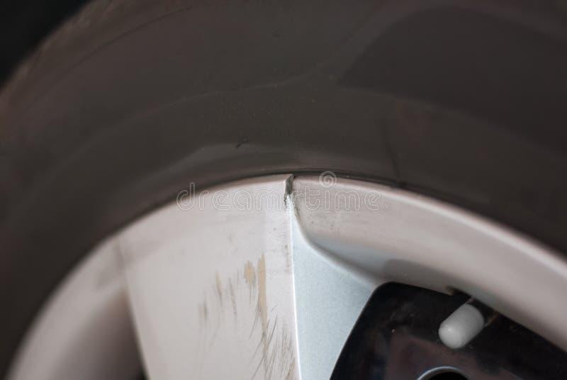 El borde de plata del neumático de coche es quebrado y rasguñado debido al golpe de s imagen de archivo