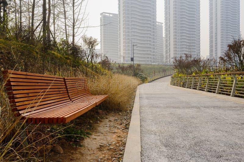 El borde del camino benches antes de edificios de la ciudad en invierno de niebla imagen de archivo libre de regalías