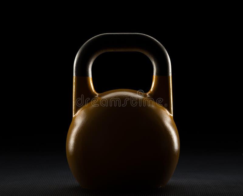 El borde encendió la silueta amarilla del kettlebell de la competencia en un piso del gimnasio del entrenamiento del peso foto de archivo