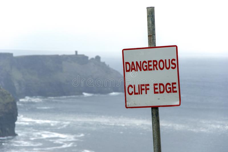 El borde peligroso del acantilado firma adentro el tiempo cubierto en los acantilados de Moher en Irlanda Advertencia de la muest foto de archivo