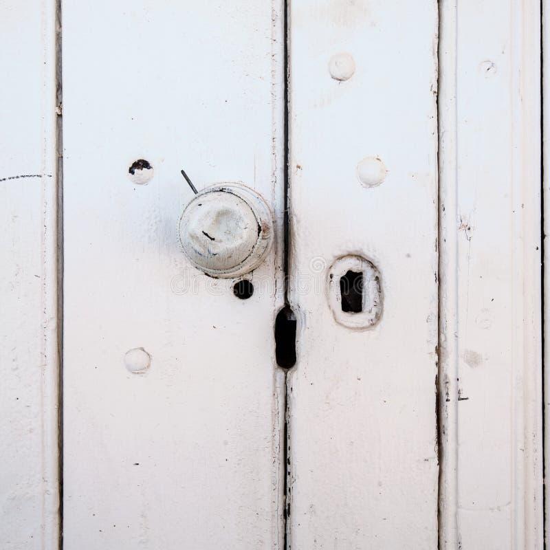 El botón de puerta abollado en un viejo pintó la puerta de madera imagenes de archivo