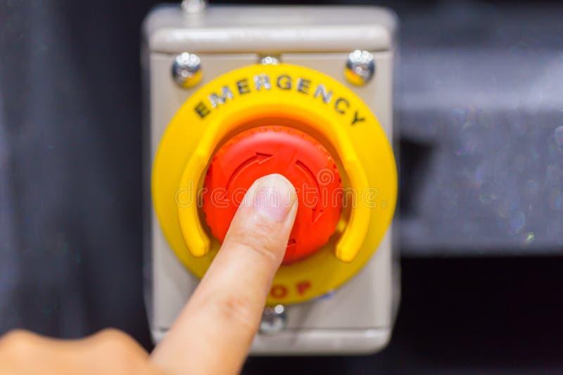 El botón rojo de la emergencia o botón de paro para la prensa de la mano El botón de paro para la máquina industrial imagen de archivo