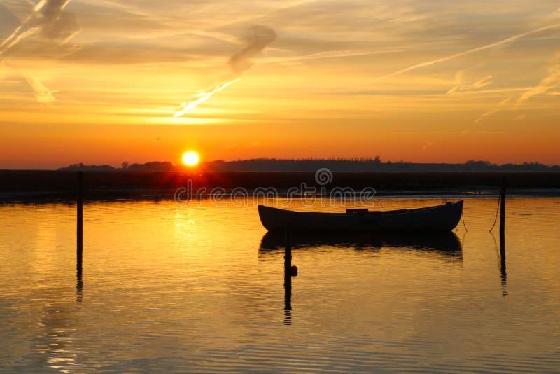 El bote abraza la puesta del sol tan hermosa imagen de archivo