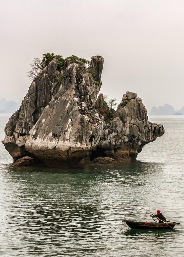 El bote de remos solitario viaja delante de roca espectacular de la piedra caliza imagenes de archivo