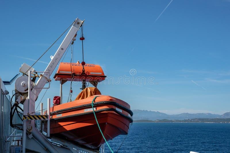 El bote salvavidas rojo del bote de salvamento se coloca en cubierta de un transbordador fotografía de archivo