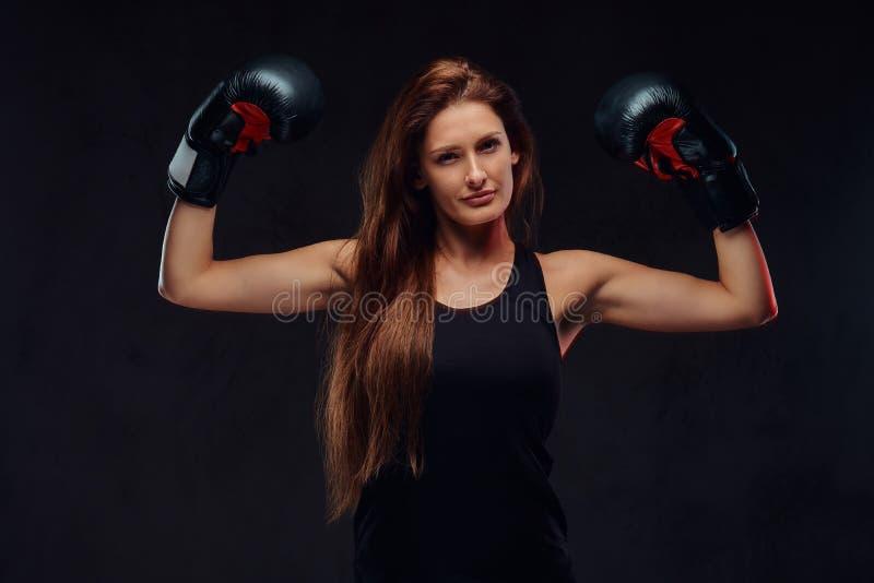 El boxeador de sexo femenino juguetón hermoso en los guantes de boxeo de la ropa de deportes que llevan, demostraciones muscles A fotografía de archivo