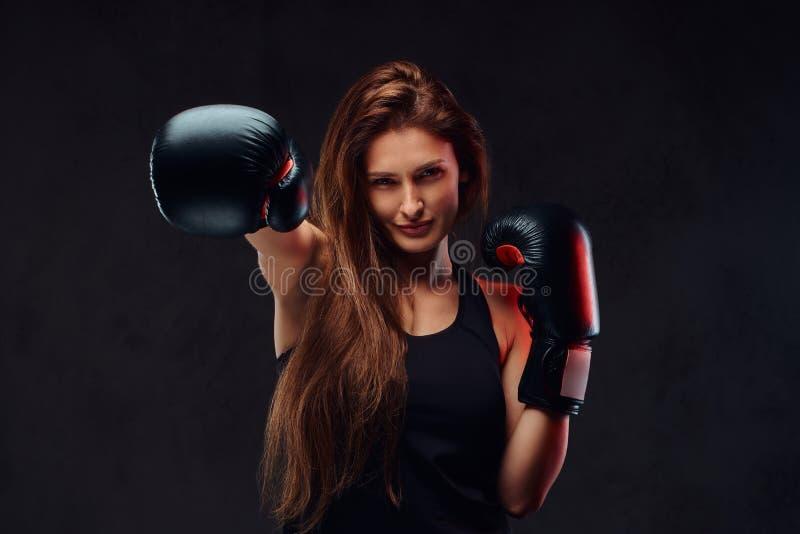 El boxeador de sexo femenino moreno hermoso durante el boxeo ejercita, entrenamiento en gimnasio Aislado en fondo texturizado osc fotos de archivo