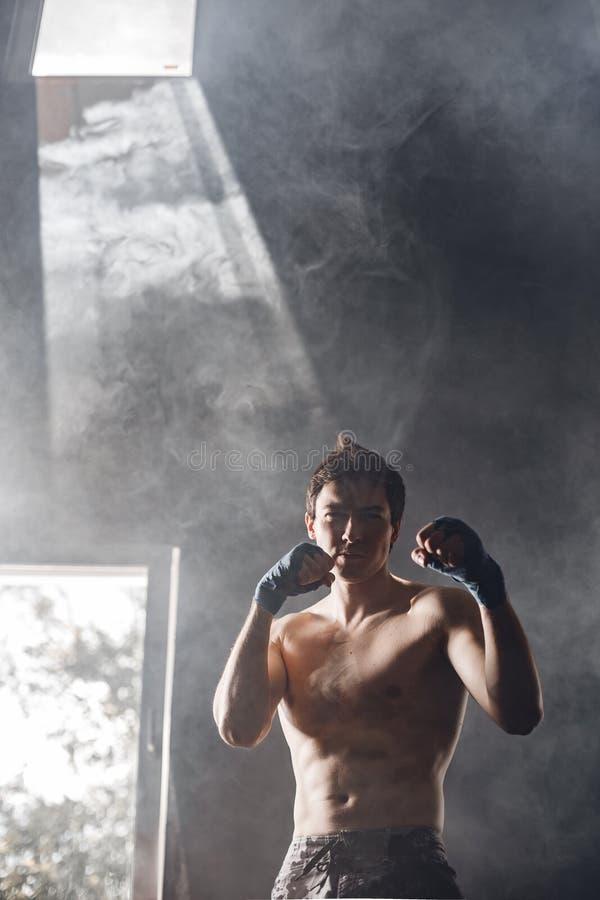 El boxeador fuerte en los rayos del sol y del humo entrena en el gimnasio imagen de archivo libre de regalías