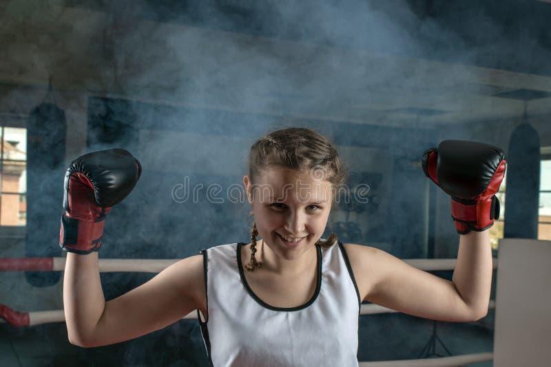 El boxeador hermoso joven de la muchacha que sonre?a feliz aument? sus manos para arriba con un gesto de la victoria fotografía de archivo