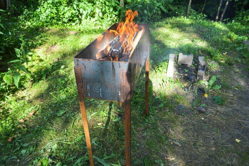El brasero grande del metal del arrabio del hierro para los kebabs de la comida campestre de la barbacoa de la parrilla con la qu fotografía de archivo