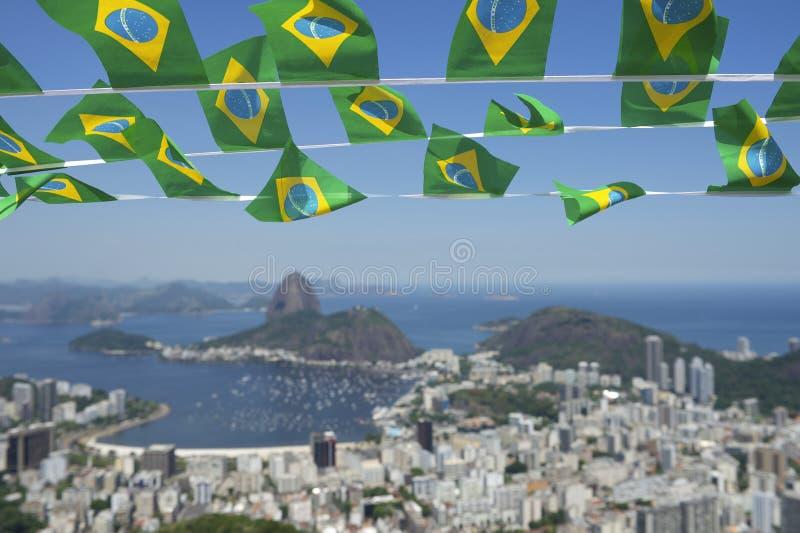 El brasileño señala a Rio de Janeiro Brazil Skyline por medio de una bandera imagen de archivo