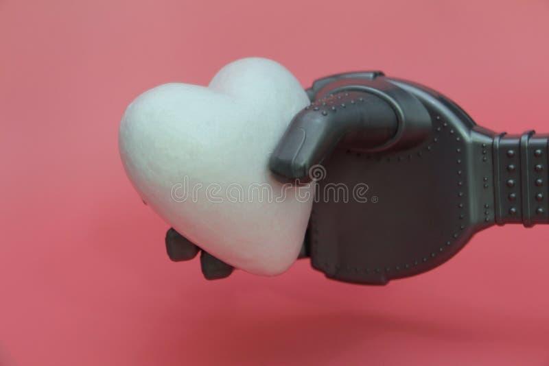 El brazo del hierro de un robot lleva a cabo un corazón blanco Concepto de robots con un corazón fotos de archivo libres de regalías