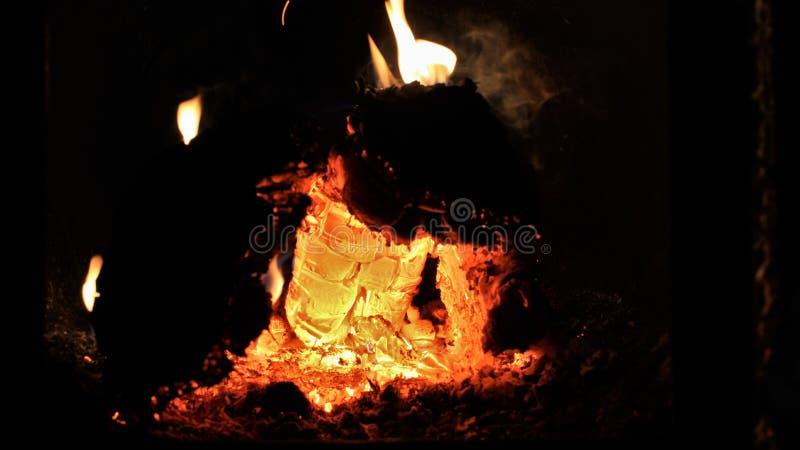 El brillar intensamente carbones anaranjados y rojos dentro de un horno de madera caliente fotos de archivo libres de regalías