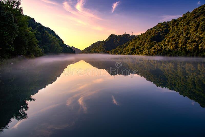El brillo de oro del sol en los árboles verdes está en la colina, una reflexión en el lago tranquilo, debajo del cielo azul y de  fotografía de archivo