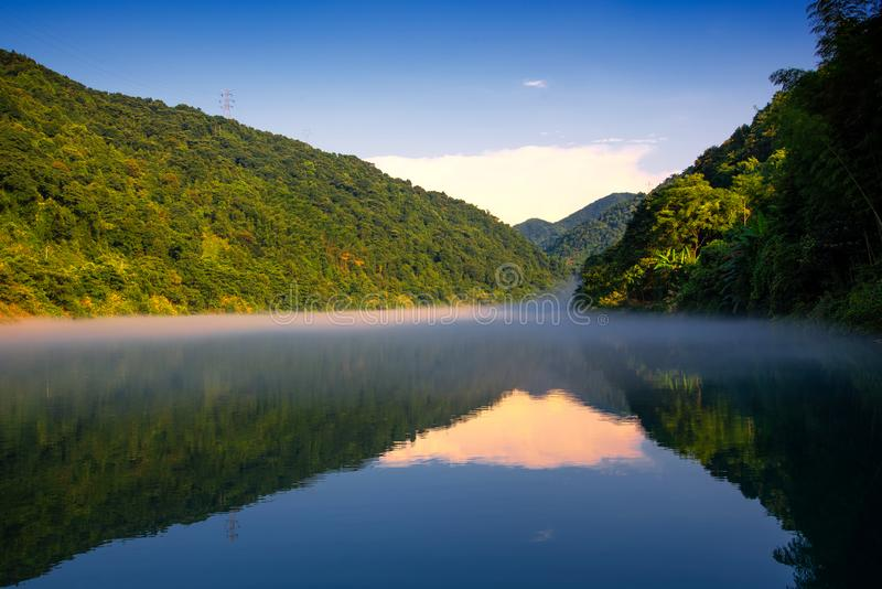 El brillo de oro del sol en los ?rboles verdes est? en la colina, una reflexi?n en el lago tranquilo, debajo del cielo azul y de  imagen de archivo