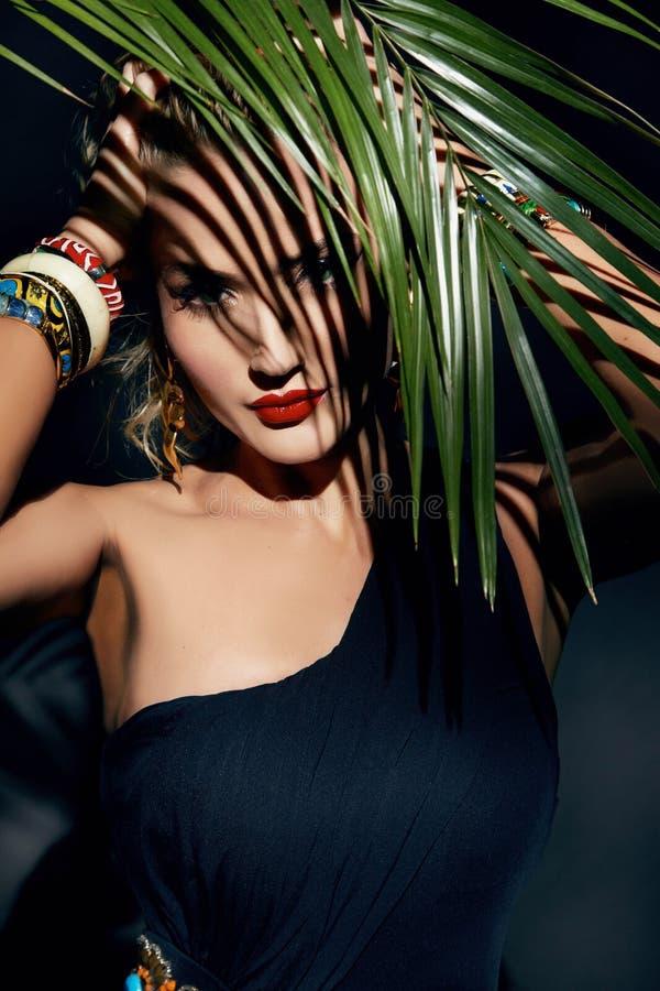 El bronceado atractivo de la palma de la selva del maquillaje de la mujer de la belleza sombrea la playa imagenes de archivo