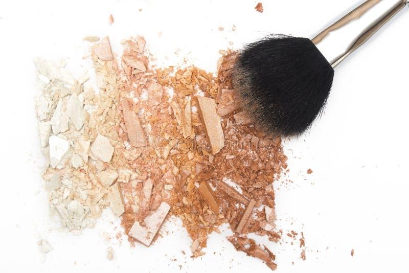 El bronzer machacado del polvo se ruboriza y pulveriza el cepillo en el fondo blanco foto de archivo