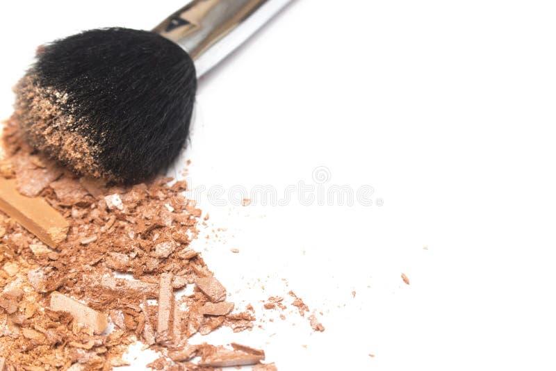 El bronzer machacado del polvo se ruboriza y pulveriza el cepillo en el fondo blanco fotografía de archivo