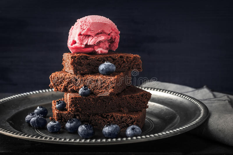 El brownie del chocolate con el arándano y el helado en el vintage platean horizontal imagen de archivo