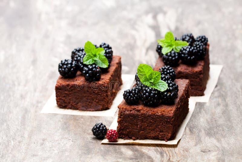 El brownie del chocolate junta las piezas con las zarzamoras en la tabla de madera foto de archivo